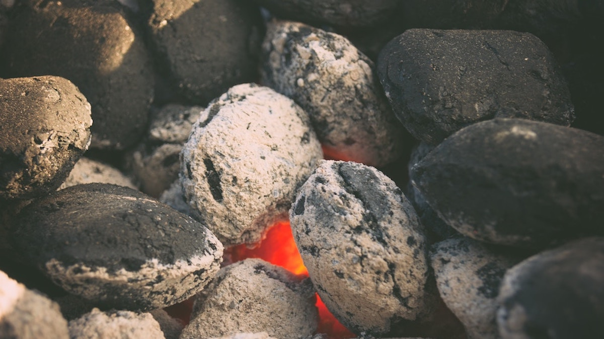 lit charcoal briquettes in a smoker